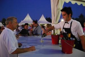 Un camarero sirve un vino en la Muestra Gastronómica. JLP.