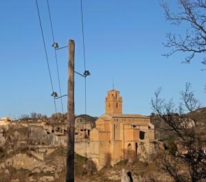 Poste de madera con la iglesia de Naval al fondo. Héctor Jiménez.