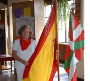 La cónsul sujeta la bandera española.