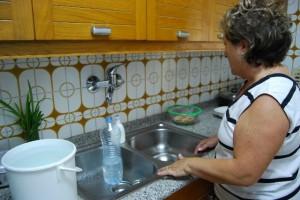 Una montisonense intenta llenar una botella de agua. Foto JLP.