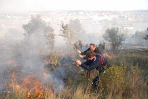 Dos vecinos tratan de apagar el incendio. JLP.