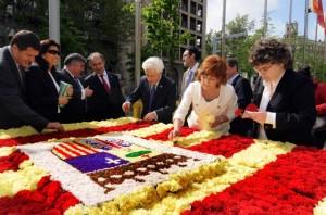 La consejera Broto junto al Justicia confeccionan la bandera de Aragón con flores.