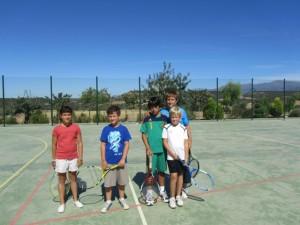 Un grupo de niños practican tenis.