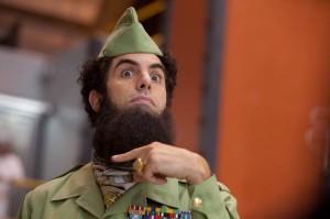 """El General Almirante Haffaz Aladeen (Sacha Baron Cohen) es un dictador capaz de arriesgar su vida para impedir que la democracia se establezca en el país al que oprime tan amorosamente y con tanto cariño. Rico en petróleo y bastante aislado, el estado norteafricano de Wadiya lleva siendo gobernado por el vehementemente anti-occidental Aladeen desde que éste tenía seis años, cuando fue nombrado Líder Supremo tras la desafortunada muerte de su padre, muerto por desgracia en un accidente de caza, alcanzado por 97 balas y una granada de mano. Desde que accedió al poder absoluto, el consejero de más confianza de Aladeen es su tío Tamir (Ben Kingsley), quien ejerce de Jefe de la Policía Secreta, Jefe de Seguridad y Proveedor de Mujeres. Por desgracia para Aladeen y sus consejeros, el muy vilipendiado Occidente ha comenzado a meter las narices en los asuntos de Wadiya, y las Naciones Unidas han sancionado repetidas veces al país en la última década, pero el Dictador no va a consentir que un inspector del Consejo de Seguridad entre en sus instalaciones secretas de armamento... ¿es que acaso no saben lo que quiere decir """"secreto""""? Pero después de que un intento de asesinarle le cueste la vida a otro de los acólitos del Líder Supremo, Tamir convence a Aladeen de que vaya a Nueva York a solucionar la cuestión de las Naciones Unidas. (FILMAFFINITY)"""